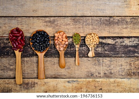 Beans on a wooden spoon with a shallow depth of field.  - stock photo