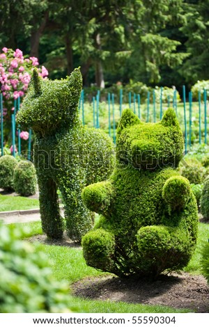 Bear and Unicorn shaped bushes in a topiary garden - stock photo