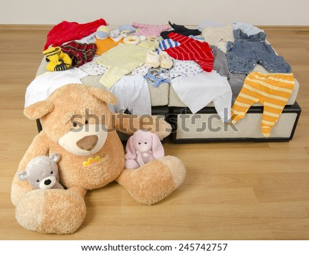 Bear toy on a bed with different colorful new born clothes.Colorful wardrobe of newborn,kids, babies full of all clothes, shoes,accessories and toys - stock photo