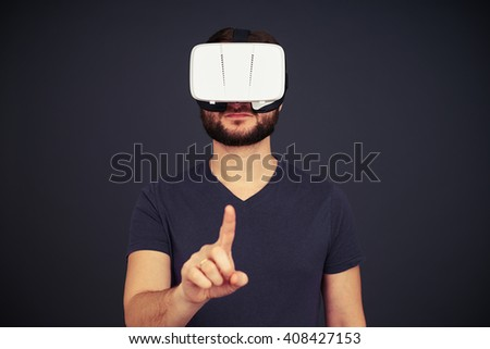 Beard man in black t-shirt is touching something with his right hand using virtual reality glasses, on black background - stock photo