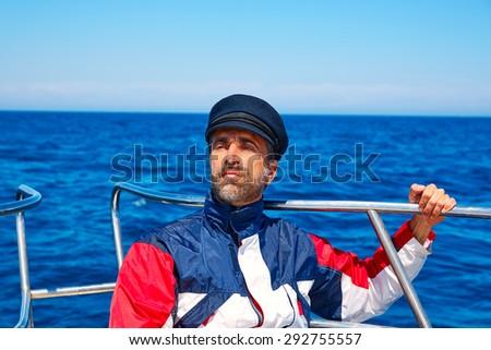 Beard sailor man sailing sea ocean in a boat with captain cap looking horizon - stock photo
