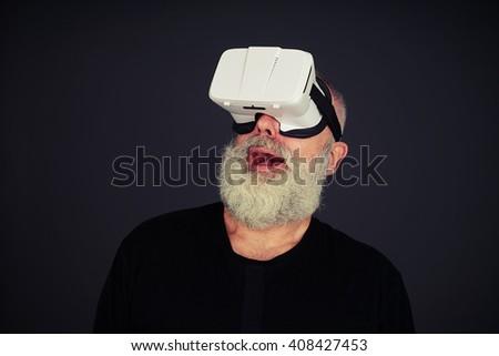 Beard senior man looking up surprised using virtual reality glasses, on black background - stock photo