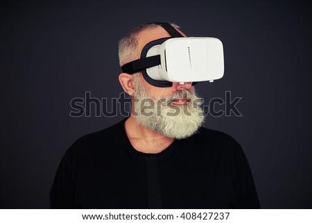 Beard senior man wearing hi-tech VR headset, on black background - stock photo