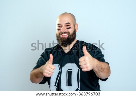 bearded american football player with thumbs up - stock photo