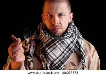Bearded army officer wearing camo clothes and smoking cigar - stock photo