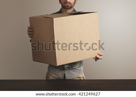 Bearded brutal courier in jeans work jacket holds big carton paper box with goods above wooden table. Special delivery, retail shipping post box - stock photo