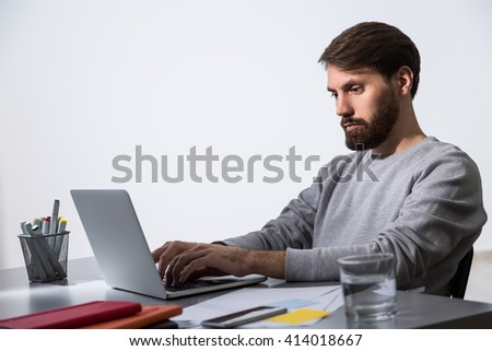 Bearded businessman working on laptop at office desk with glass of water and office tools. Sideview - stock photo