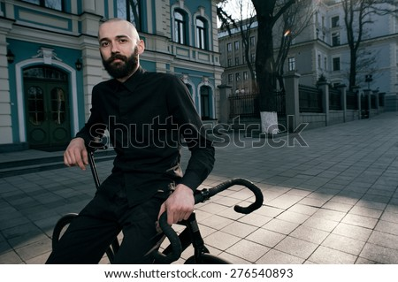 bearded caucasian bald man sits on black fix bicycle near old restored building. He sits in morning light in cobbled street. Street is empty. Man is wearing black shirt and trousers and sneakers.  - stock photo