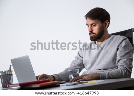 Bearded caucasian businessman working on laptop at office desk with glass of water and office tools. Sideview - stock photo