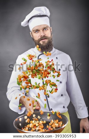 Bearded chef flipping vegetables in a frying pan over gray background - stock photo