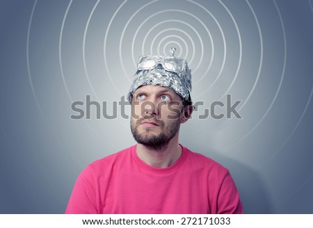 Bearded funny man in a cap of aluminum foil sends signals. Concept art phobias - stock photo