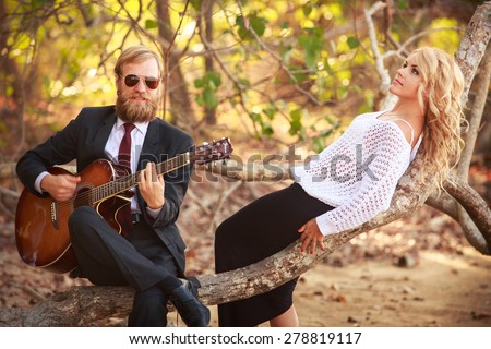 bearded guitarist in black suit and blonde girl  in purple dress sit on branch of tropical tree - stock photo