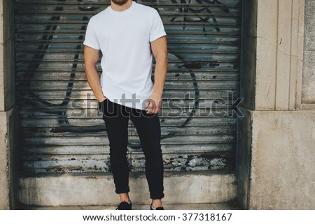 Bearded guy wearing white blank t-shirt and black jeans, standing opposite garage  - stock photo
