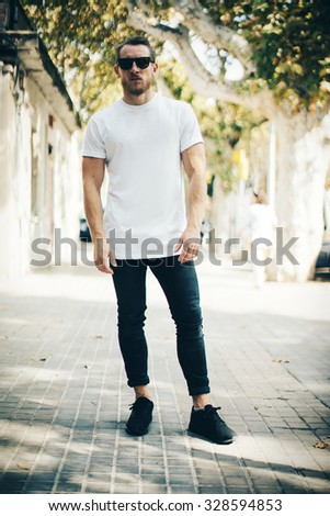 Bearded guy wearing white blank t-shirt and blue jeans - stock photo
