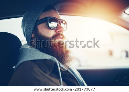 bearded hipster wearing sunglasses inside car with lens flare and retro filter - stock photo