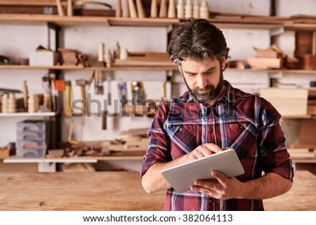 Bearded male designer, standing in his woodwork studio, working on a digital tablet, with shelves of wooden pieces behind him - stock photo