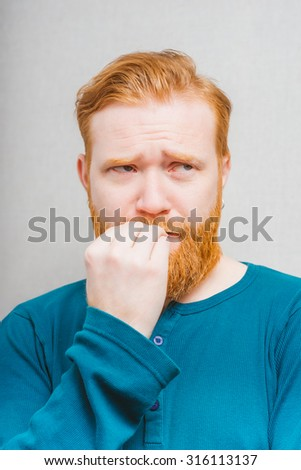bearded man going through and bites his nails - stock photo