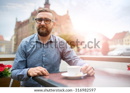 Bearded man having coffee in restaurant at market square - stock photo