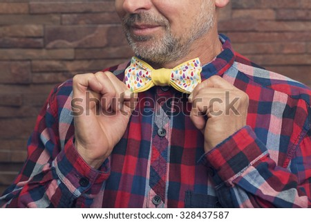 Bearded man holding a colorful bow tie - stock photo
