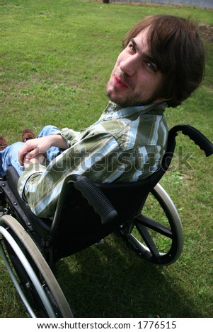 Bearded man in a wheel chair.  Has a funny expression. - stock photo