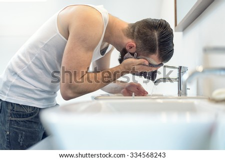 Bearded man rinsing his face in the bathroom under water from the tap in the hand basin after completing his shaving - stock photo