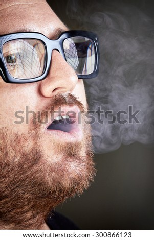 Bearded man smoking a cigarette. Bespectacled man enjoy a cigarette. Portrait of a bearded with eyeglasses smoking a cigarette. - stock photo