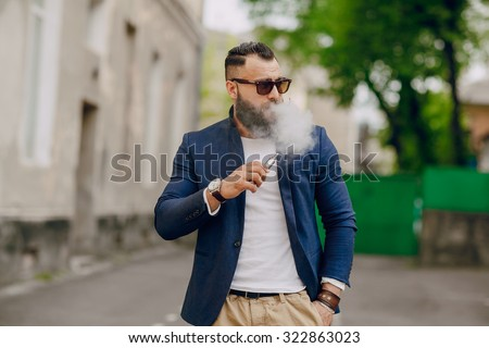 bearded man with e-cigarette outdoors - stock photo