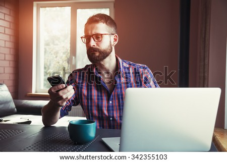 bearded man working with laptop and phone in morning sunlight - stock photo