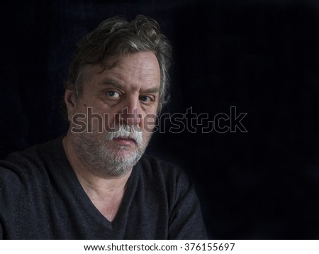 bearded middle-aged man on dark background - stock photo