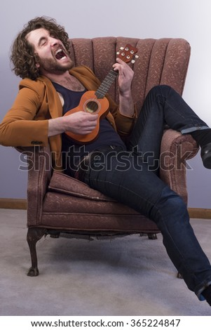 Bearded musician playing acoustic ukulele guitar in vintage chair - stock photo