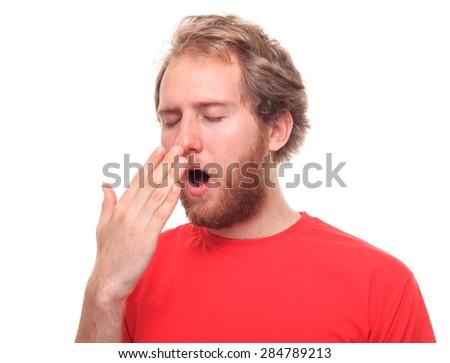 Bearded young man yawinig  - stock photo