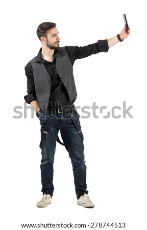 Bearded young trendy hipster guy taking selfie profile view. Full body length portrait isolated over white background.  - stock photo