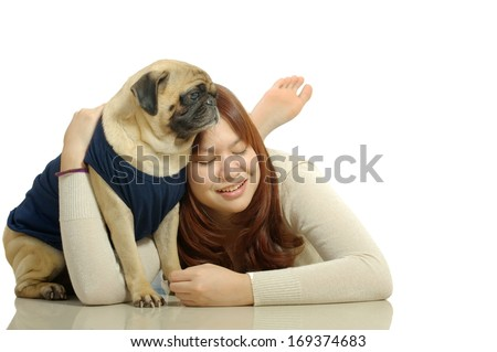 beatiful Asian teen lying down on the floor and hug pug dog with isolated white background - stock photo