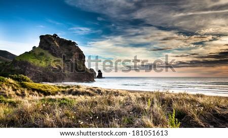 Beatiful sunset on Piha Beach, New Zealand - stock photo