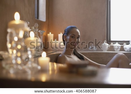 Beatiful woman in spa bath with candles - stock photo