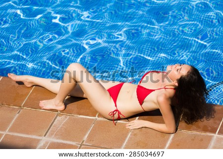Beaty woman relax near swimming pool on sunny day - stock photo