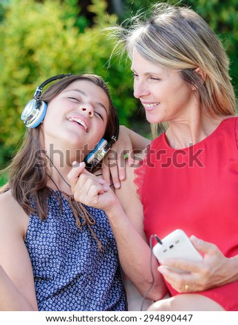 beautful young girl with her mother listening music together with complicity - stock photo