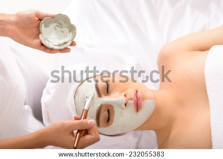 Beautician applying facial mask to the young lady, view from the top - stock photo