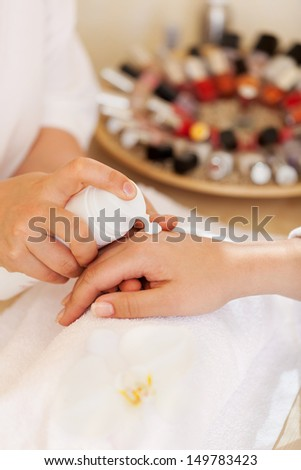 Beautician applying hand cream during a manicure in a salon from a pump bottle, close up view of hands - stock photo