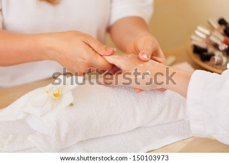 beautician applying lotion on women's hand - stock photo