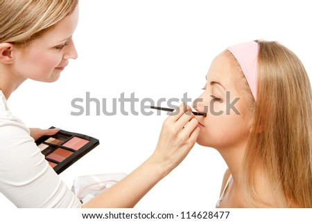 Beautician Applying Woman's Make Up.Isolated on white - stock photo