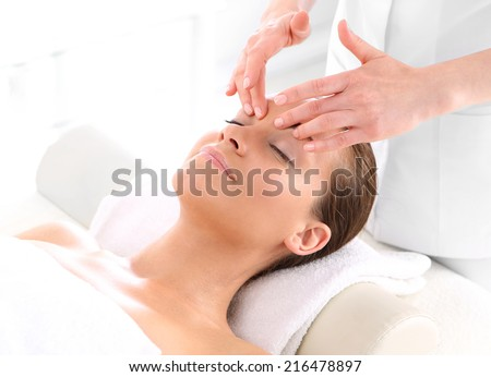 Beautician beautiful woman massaging her temples .Attractive brunette woman in spa salon. - stock photo