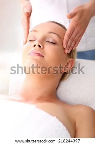 Beautician beautiful woman massaging her temples . Woman in a beauty salon. Masseur massaging a woman in a spa. - stock photo