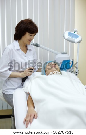 Beautician conducts a session of skin treatment. - stock photo
