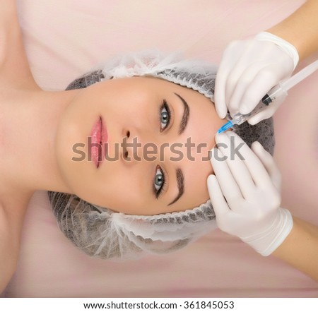 Beautician examining the face of a young female client at spa salon. beautician beauty injections. Professional consultation.  - stock photo