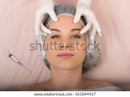 Beautician examining the face of a young female client at spa salon. Professional consultation.  - stock photo