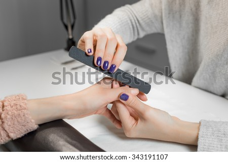 Beautician filing female clients thumb and nails at spa beauty salon.Manicurist work on pure white table with professional tools for manicure and pedicure. - stock photo