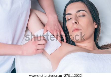 Beautician hands doing depilation armpit to beautiful woman with wax strip in a beauty salon - stock photo