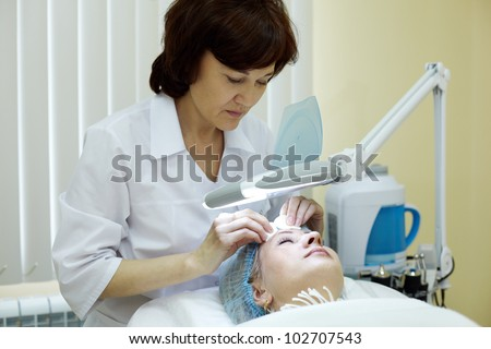 Beautician in beauty salon cleans facial skin of woman. - stock photo
