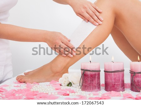 Beautician Waxing A Woman's Leg Applying Wax Strip - stock photo